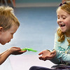 BRYAN EATON/Staff photo. Jeremy Doiron, 5, blows a feather for Maeve Goldson, 6, to catch and she to continue around the circle, another breathing excercise.