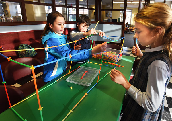 BRYAN EATON/Staff photo. Creating an obstacle course out of plastic tubes are, from left, Fiona DeLisle, 10, Collin Courtney, 9, and Eloise LeDuc, 10. They were in the Children's Room at the Newburyport Public Library on Tuesday afternoon working on STEM Structures where they used their imagination and teamwork to create things.