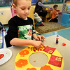 BRYAN EATON/Staff photo. Oilver Bonafede, 5, decorates a Chinese New Year wreath in Mary Jo Lagana's pre-kindergarten class at Newbury Elementary School on Thursday. The wreaths are hung on doors to welcome guests for the holiday which begins on February 19 this year which is year of the pig.