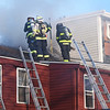 BRYAN EATON/Staff photo. Firefighters are positioned on the roof of the rowhouse adjacent to 155 High Street at right to attack the fire in the rear of the buildings.