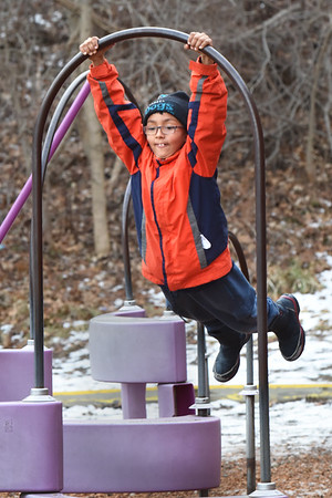 BRYAN EATON/Staff photo. Quinn Gafur, 8, swings on playground equipment at Amesbury Elementary School on Friday afternoon. He was in the Amesbury Youth Recreational Department's Afterschool Program which moved activites outside as the weather was seasonable.