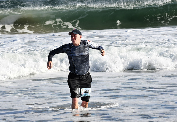 JIM VAIKNORAS/Staff photo.. takes a swim in the ocean after finishing the Hangover Classic at Salisbury Beach Tuesday. Most runners just went in knee deep due to  warnings about high surf and an undertow.
