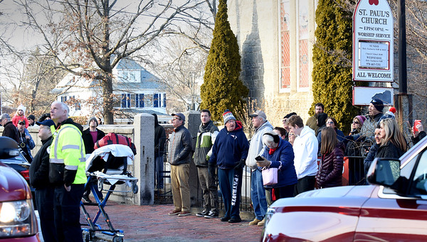 BRYAN EATON/Staff photo. People gathered in front of St. Paul's Church to watch firefighters tackle the smoky fire.