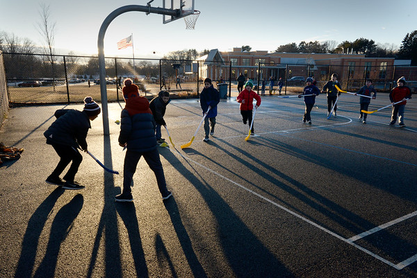 BRYAN EATON/Staff photo. Youngsters in the Newburyport YWCA Afterschool Program play some street hockey at the basketball court at the Bresnahan School late Thursday afternoon. The court was still wet from the snow that fell earlier in the day.