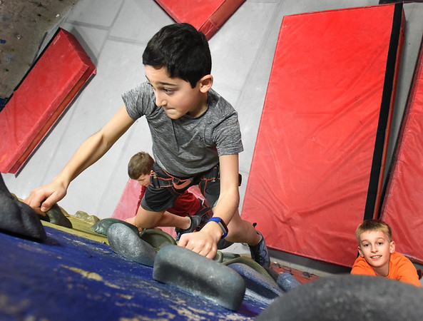 BRYAN EATON/Staff photo. Jared Newman, 10, looks for a handhold followed by Logan MacKnight, 9, left, and Tyson Stroope, 10, as they climb one of the walls at MetroRock climbing center in Newburyport. They were with Newburyport Youth Services which goes there every Tuesday for a six-week program.