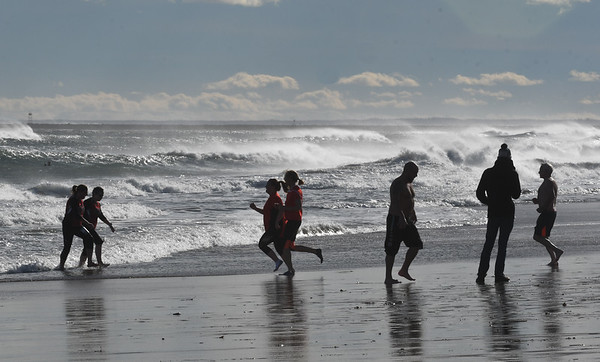 JIM VAIKNORAS/Staff photo Runners take a swim in the ocean after finishing the Hangover Classic at Salisbury Beach Tuesday. Most runners just went in knee deep due to  warnings about high surf and an undertow.