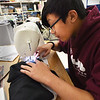 BRYAN EATON/Staff photo. Trevian Vo, 15, of Salisbury sews pockets into a sweatshirt he has been working on the past two weeks.