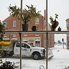 JIM VAIKNORAS/Staff photo A plows heads down Water Street in Newburyport past the window at Souffles Sunday morning.