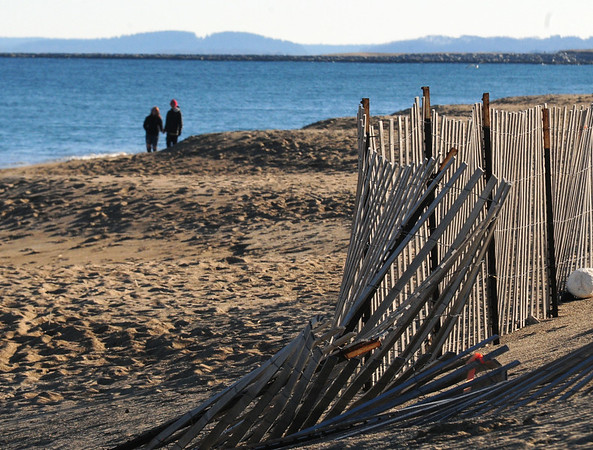 JIM VAIKNORAS/Staff photo A couple takes advantage of the sunny weather to walk along Salisbury Beach Sunday afternoon.