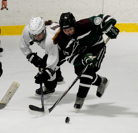 JIM VAIKNORAS/Staff photo North Andover's Morgan Flaherty fights for the puck with a Billerica/Chelmsford player Wednesday night at Veteran's Rink in Haverhill