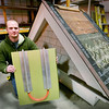 BRYAN EATON/Staff photo. The Chestnut Street Innovation Center in Amesbury has grown to 75 percent capacity. Caleb Reninger of INroof.Solar shows the underside section of a metal roof panel. The black tops of the metal roofing absorb heat from the sun and transfers it to the piping to be pumped into plumbing of the home.