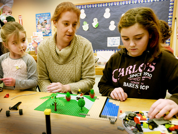 BRYAN EATON/Staff photo. New Seabrook Public Library children's librarian Gretyl Macalaster in LEGO club with Abigail Merrill, 4, left, and Phoebe White, 10.