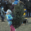 JIM VAIKNORAS/Staff photo Solange Poupou of Newburyport gets ready to toss a Christmas Tree at the Annual Old Newbury Christmas Tree Bonfire at the Tendercrop Farm growing fields Saturday night. Along with game, the event included local food and drink venders an auction, photo booth, and of course an enormous fire.