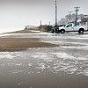 BRYAN EATON/Staff photo. A Salisbury town truck pushes back sand as ocean waves spilled over to the Salisbury Beach center on Monday just before high tide.