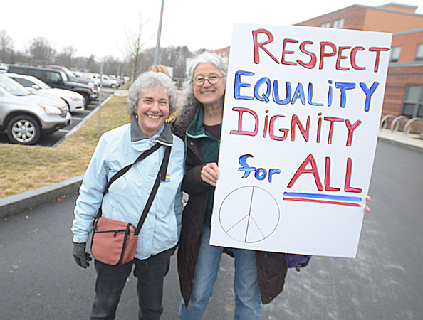 JIM VAIKNORAS/Staff photo Mary Williamson sign up riders at the Bresnahan School Saturday morning.Over 260 people board 5 buses  headed to the Women's March in Boston.