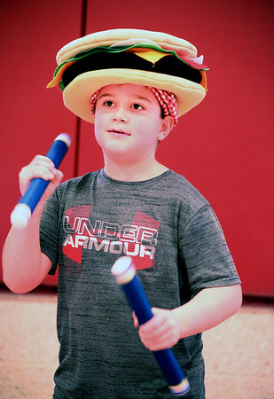 """BRYAN EATON/Staff photo. William Hansen, 8, shakes batons during an excercise demonstration by third-graders at a community assembly at the Bresnahan School which they have every six weeks where they promote district-wide """"Clipper Values."""" Perseverance was the value discussed Monday and the students demonstrated it doing their excercises. The younster was wearing a """"cheeseburger hat"""" as it was also Hat Day at the Newburyport school."""