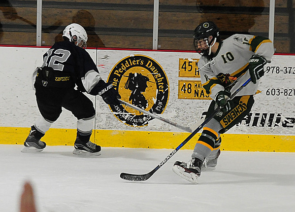 JIM VAIKNORAS/Staff photo Hamilton's cameron Vautour fights for the puck with Pentucket's Johnny Orlando Saturday in Haverhill.
