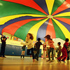 BRYAN EATON/Staff photo. Second-graders in Margaret Welch's physical education class at Amesbury Elementary did different activities using a parachute to learn teamwork and coordination on Wednesday afternoon. In this excercise the younsgters pulled the parachute as high as they could with several taking turns running into the center and back before it collapsed on them.