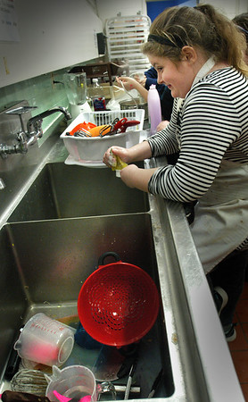 BRYAN EATON/Staff photo. Cooking With Carol is always a popular program with Carol Chiungos at the Boys and Girls Club where they were making soup and salad creations on Tuesday. But with cooking comes cleaning dishes and it was Jaclyn Zinck's turn for the chore this time.