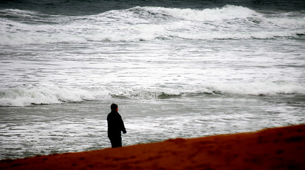 JIM VAIKNORAS/Staff photo A woman walks along a stormy Salisbury Beach Sunday morning. Although the weather has been unseasonably warm, the clouds and rain gave the beach a raw look and feel.