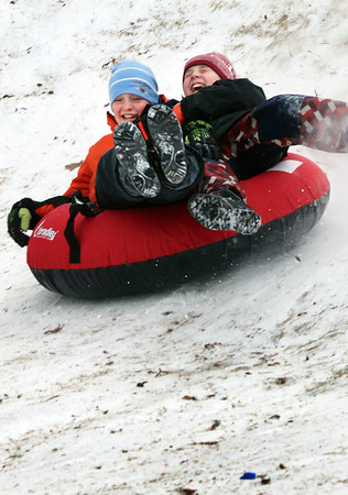 BRYAN EATON/Staff photo. James Forrest-Hay, left, in orange, and friend Ibo Sava, both 12, slide down March's Hill in Newburyport on Monday afternoon on snow from the weekend's storm. The snow should disappear later in the week as rain is expected with temperatures in the upper 50's.