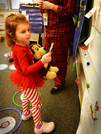 """BRYAN EATON/Staff photo. Avery Herdman, 4, with doll Kaya, goes up to vote for pancakes over waffles in Julie Deschene's preschool class on Thursday morning. It was Pajama Day and she read the children """"When You Give a Pig a Pancake"""" after which they got to help make the breakfast of their choice."""