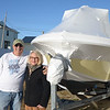 JIM VAIKNORAS/Staff photo Anthony and Jane Coletti stand  outside their home with their boat in the Seabrook Beach Village District. Coletti recently won a law suit allowing him to keep his boat in his driveway.