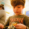 BRYAN EATON/Staff photo. Camden Desch, 7, of Newburyport ties yarn around two popsicle sticks as he makes God's Eyes on Tuesday afternoon. He was in the Newburyport YWCA's School's Out Program in the craft section at the Bresnahan School.