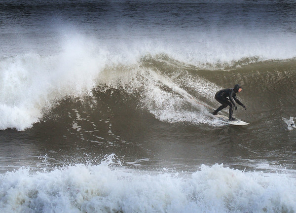 BRYAN EATON/Staff photo. High waves at Salisbury Beach attracted a half dozen surfers to head in the water just north of the Blue Ocean Event Center on Wednesday afternoon.