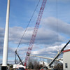 BRYAN EATON/Staff photo. A crane lowers the blades of the wind turbine at Mark Richey Woodworking to the ground at right. Crews are repairing the electricity generator which should take a week.