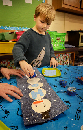 """BRYAN EATON/Staff photo. Henry Maneikis, 5, uses letter blocks dipped in paint to spell out his name on a snowman with the help of teacher's aide Joyce Alders at Newbury Elementary School. The students in Jennifer Townsend's kindergarten class were working on """"literacy centers,"""" which used different activities that helped teach spelling."""