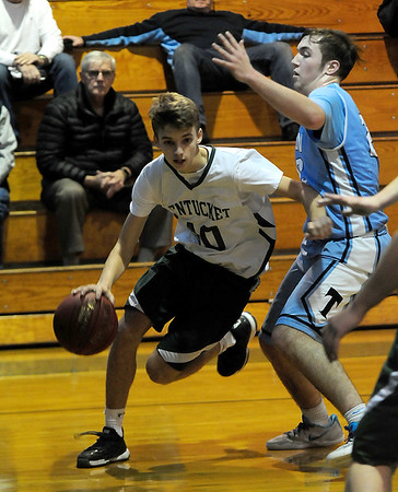 JIM VAIKNORAS/Staff photo Pentucket's Sam Stys dives teh baseline on Triton's  William Parsons during their game at Pentucket Wednesday.
