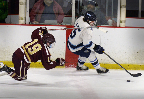 BRYAN EATON/Staff photo. Triton's Jake Daniels gets the puck away from Cole Spence.