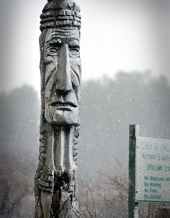 BRYAN EATON/Staff photo. The totem pole at the entrance to Battis Farm in Amesbury gets coated with a little snow on Monday for heavy rain overnight was forecast to wash it away.