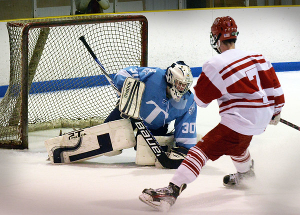 BRYAN EATON/Staff photo. Triton goalie Ben Fougere stops a shot by Masconomet's Jake McKenna.