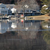 BRYAN EATON/Staff photo. Melting ice on Lake Gardner is Amesbury reflects the houses on Whitehall Road. The weather gets colder again over the weekend with yet another warmup mid-week.