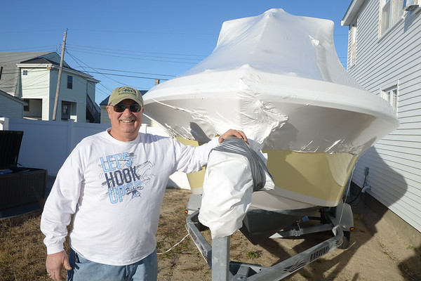 JIM VAIKNORAS/Staff photo Anthony Coletti stands outside their home with their boat in the Seabrook Beach Village District. Coletti recently won a law suit allowing him to keep his boat in his driveway.