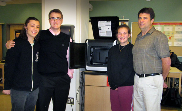 JIM SULLIVAN/Staff photo. Amesbury High School engineering students from left to right, Chris Marrama, Jacob Robicheau, Kayleigh Hooper and engineering/technology teacher Jim Gallante stand in front of a 3D printer.
