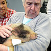 JIM VAIKNORAS/Staff photo Peg Sparks holds Charlie the pig the Senior Center in Amesbury. Sparks was one of about 40 who showed up to meet and pet the animals brought by Animal Craze Traveling Farm Friday.