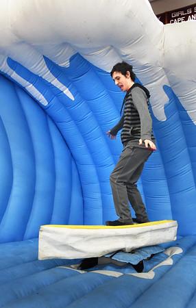 BRYAN EATON/Staff photo. Mike Walker, 16, tries to keep his balance on a mechanical surfboard.