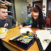 BRYAN EATON/Staff photo. Elijah Jackman, left, and Sierra Cote, both 19, work on flyers that contain more information that the billboards being created for the public relations campaign at the Amesbury Innovation High School.