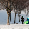 JIM VAIKNORAS/staff photo Sledders make their way to the Mall in Newburyport on a sunny, cold and windy Friday afternoon.