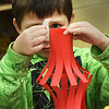 BRYAN EATON/Staff photo. Alex Chernick, 7, tapes a handle to his Chinese New Year's lantern at the Boys and Girls Club on Tuesday afternoon, one of several art projects going on in the art room. Chinese New Year starts on February 16 and it is the year of the dog.