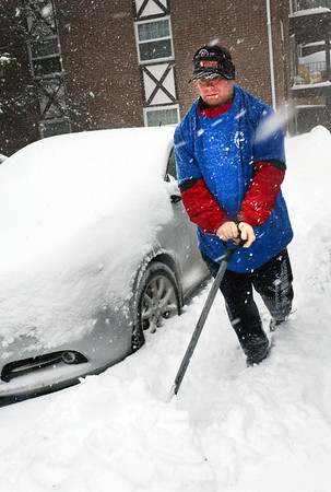 BRYAN EATON/Staff photo. Jim Murphy shovels snow for an elderly person at Tudor Manors in Seabrook.