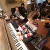 "JIM VAIKNORAS/Staff photo Henry Louis Grady, 7, plays ""Good King Wenceslas"" for his teacher Penny Lazarus and his fellow piano students at Lazarus's home in Newburyport Saturday. The students gathered to sort music for a free library in front of the house on Merrimac Street."