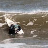 JIM VAIKNORAS/Staff photo Austin Stevens of Salisbury climbs back on his board as he surfs off Salisbury beach Friday afternoon. At the time of the photo it was 14 degrees with a 20 MPH wind putting the wind chill at -4.