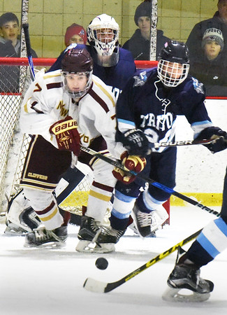 BRYAN EATON/Staff photo. Newburyport's Patrick Leary, left, and a Triton player go for a loose puck.