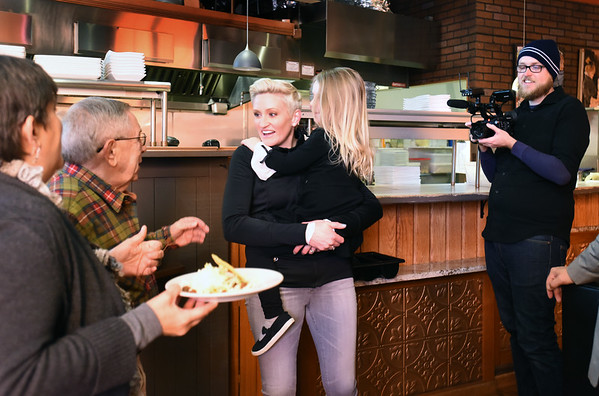 """BRYAN EATON/Staff photo. """"Small Business Revolution-Main Street"""" photographer Scott Thompson films host Amanda Brinkman meeting members of the Amesbury Rotary Club at Crave restaurant while holding owner Sean Toomey's daughter, Hannah, 4."""