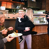 "BRYAN EATON/Staff photo. ""Small Business Revolution-Main Street"" photographer Scott Thompson films host Amanda Brinkman meeting members of the Amesbury Rotary Club at Crave restaurant while holding owner Sean Toomey's daughter, Hannah, 4."