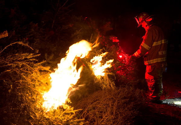 JIM VAIKNORAS/Staff photo Newbury Fire Fighter Tim Wareham lights the fire at the Old Newbury Christmas tree Bonfire at the Tendercrop Farm fields and Spencer Perce-Little Farm in Newbury Saturday night.